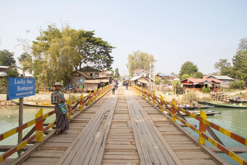 Shan State, Myanmar - 9 février 2018 : Homme non identifié se tenant sur un pont en bois plus d'une des nombreuses rivières intro photo libre de droits