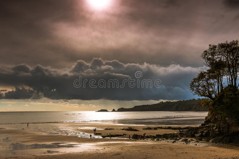 Shanahra Chronicles,Beach landscape, sun breaking through stormy skies with mountains, sea and sand, people walking. People enjoying the beach at Southerndown stock image