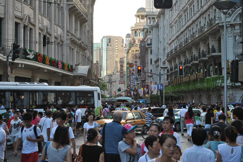 Shangai. Image of nanchino street to shangai with bright insignias and in moment of crowd and the background you see the skyscrapers stock photo