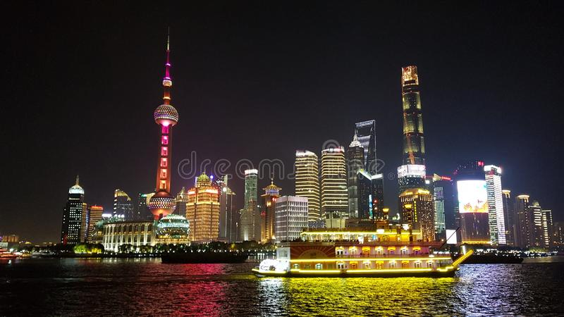 Shangai dark skyline and boat in the middle stock image