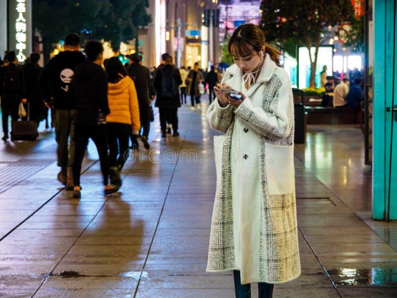 SHANGHAI, CHINA - 12 BRENG 2019 in de war – een aantrekkelijke Chinese dame op haar smartphone bij Road van Nanjing van het Ooste stock foto