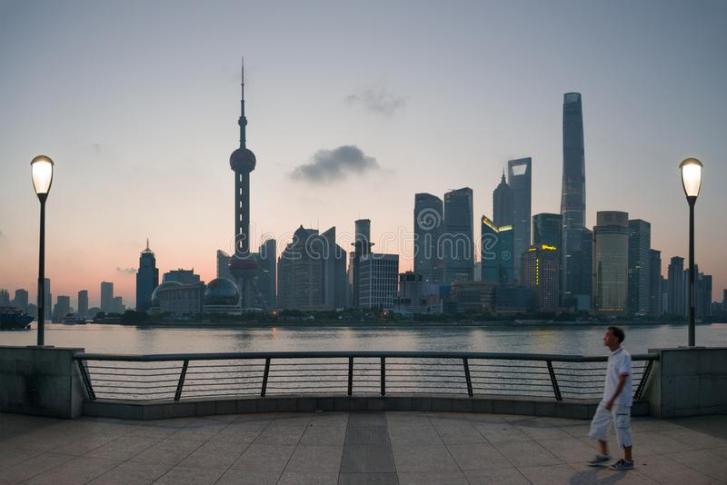 Shanghai, China - 08 27 2016: chinese man walking at The Bund early in the morning at sunrise. View of Pudong from The Bund stock photo