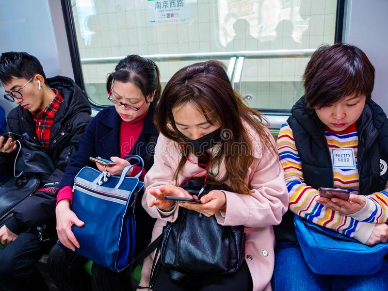 SHANGHAI, CHINA - 12 MAR 2019 - a row of commuters on the Shanghai Metro all on their smartphones. China has an extremely high stock images