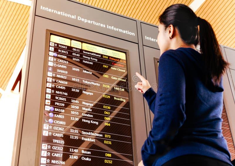 SHANGHAI, CINA - FEBBRAIO 2019: programma di volo di controllo del viaggiatore della donna nel terminale di aeroporto fotografia stock libera da diritti