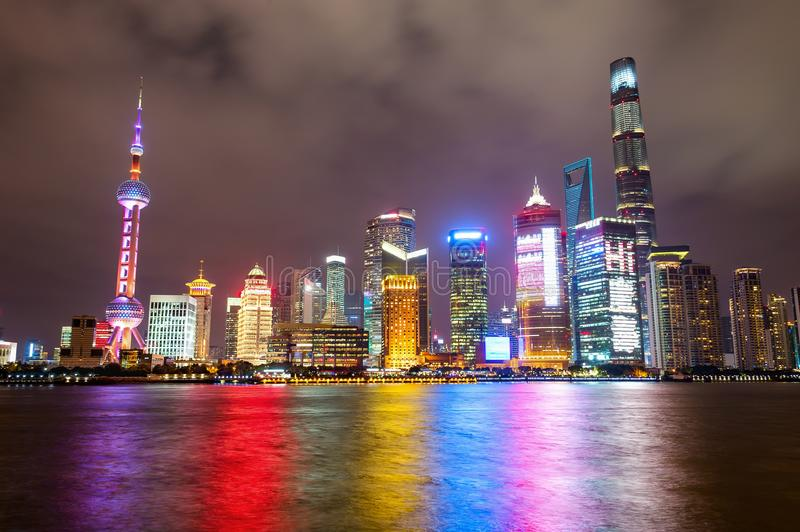 Shanghai city skyline at night. Illuminated Shanghai city skyline at night, with colorful lights reflecting on water surface royalty free stock photo