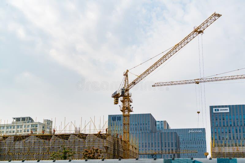 SHANGHAI KINA APRIL, 2017: En kran fungerar på byggnadskonstruktionsplats på high tech parkerar det industriella godset royaltyfri bild