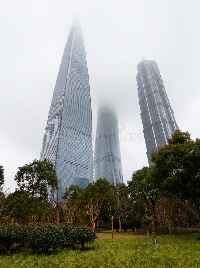 SHANGHAI KINA - JANUARI 22, 2018: Det Shanghai tornet, den finansiella mitten och Jin Mao Skyscrapers överträffar dolt vid dimma  arkivfoton