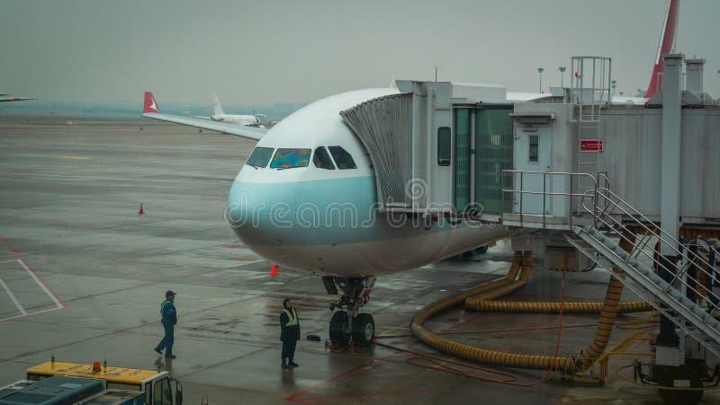 Shanghai, Kina - 28 januari 2019: Flygplan som är klart för ombordstigning på Shanghais flygplatsnav på regndagen arkivbilder