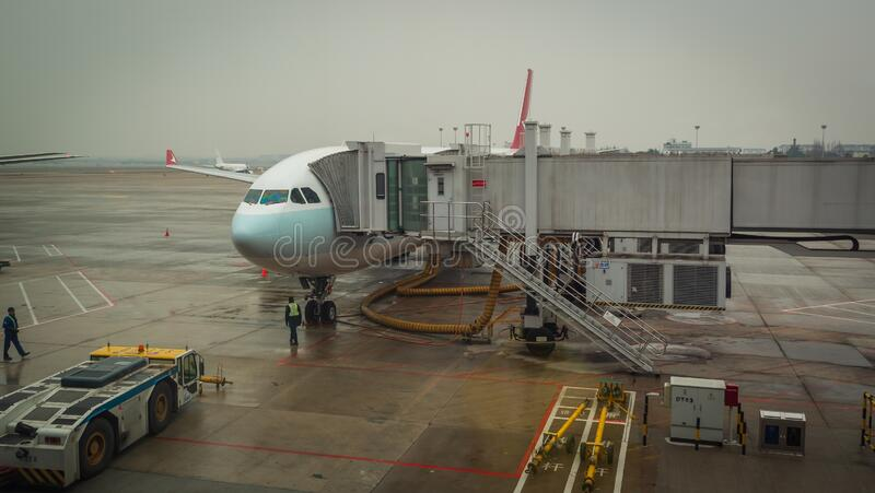 Shanghai, Kina - 28 januari 2019: Flygplan som är klart för ombordstigning på Shanghais flygplatsnav på regndagen arkivfoton