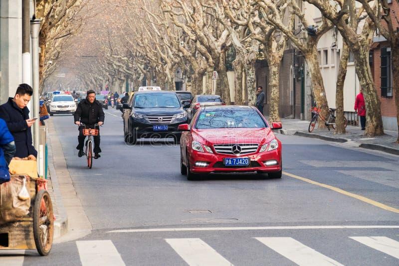 Shanghai Kina - Januari 15, 2018: gata med träd och ridningbilar och cyklister, Kina royaltyfria foton