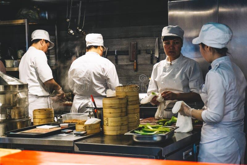 Shanghai Kina - Maj 27, 2019: Kinesiska kockar arbetar i köket av restaurangen arkivfoto