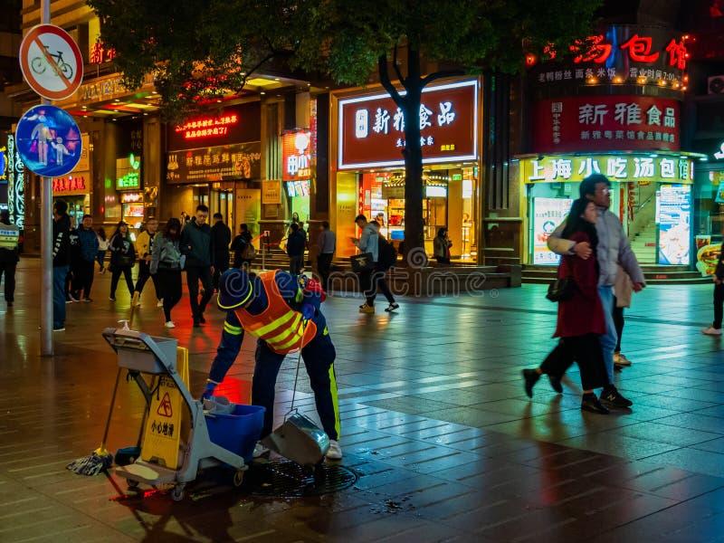 SHANGHAI KINA - 12 MARS 2019 - ett gatarengöringsmedel på Nanjing den östliga vägNanjing Dong Lu fot- gatan, Shanghai, Kina på royaltyfria bilder
