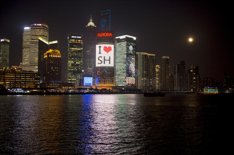 Shanghai at night with Advertising on Skyscapers of Pudong and full moon royalty free stock image