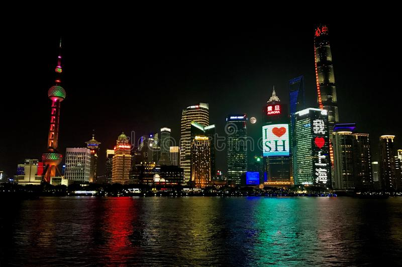 Shanghai Night Skyline With Full Moon. Pudong, Shanghai, China from across the Huangpu River. Iconic buildings including the Oriental Pearl Tower light up the stock photography