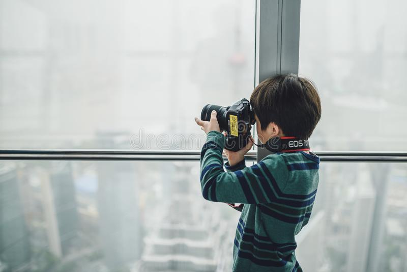 Shanghai World Financial Center building Observatory. SHANGHAI, CHINA - MAY 07, 2016: Young kid taking pictures in Shanghai World Financial Center building stock photos