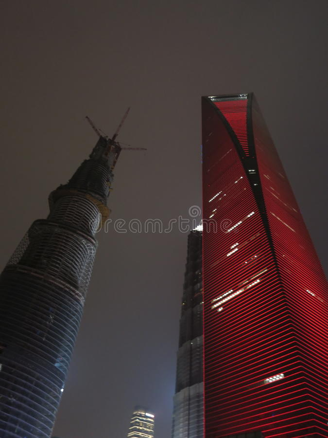The Shanghai World Financial Center and the Shanghai Tower. FEBRUARY 2013 - SHANGHAI: The Shanghai World Financial Center in red lights at night, next to the stock photos