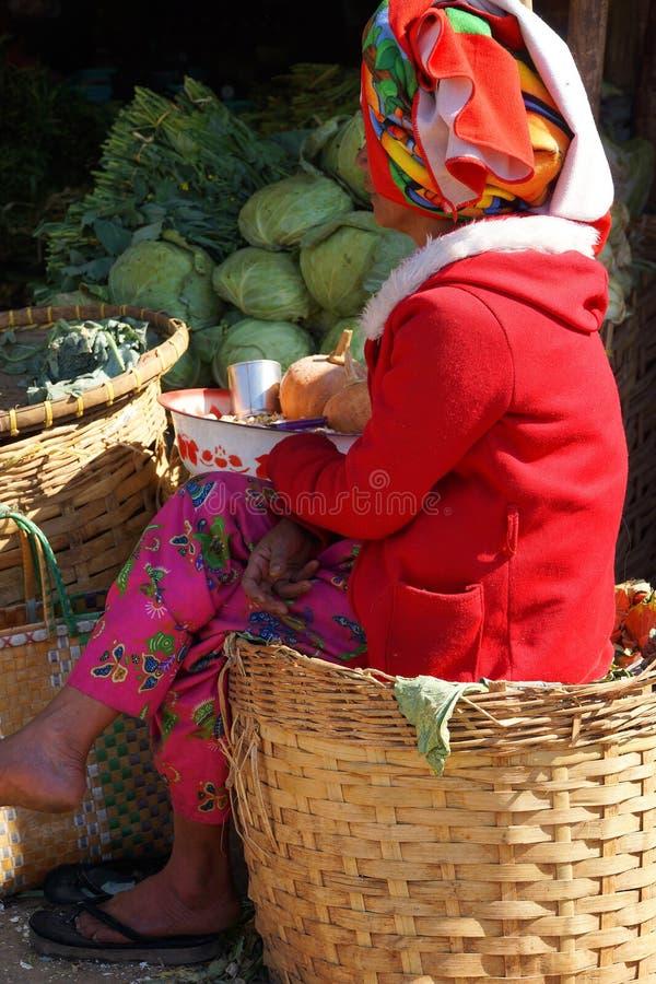 Shankvinnan ansar en grönsakställning arkivbilder