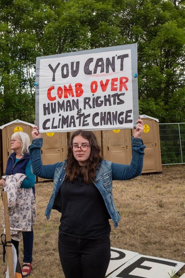 Shannon, Ierland, Juni 5, 2019: Een jonge dame die tegen het Donald Trump-bezoek met tekens in Shannon Airport, Ierland protester royalty-vrije stock foto