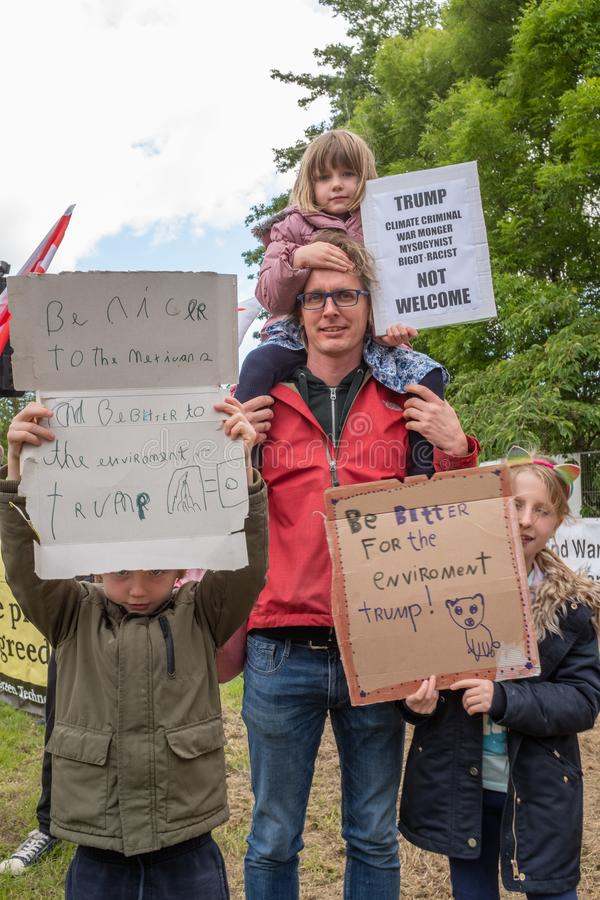 Shannon, Ireland, June. 5, 2019: A father with his young children with signs protesting against the Donald Trump visit with signs stock image