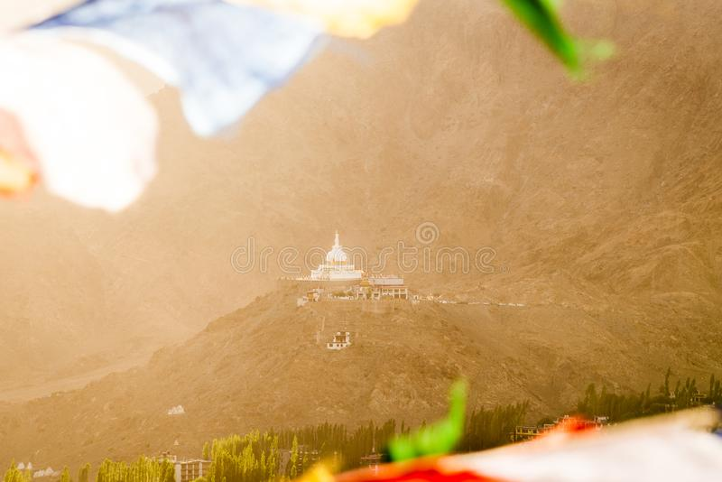 Shanti stupa through the prayer flags in sunset time with sunlight royalty free stock photos