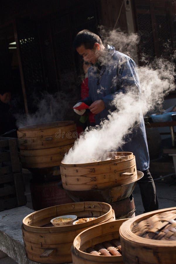 SHAOXING, CHINA: Chinese mens die traditionele lokale dimsum verkopen bij oude stad van Anchang tijdens de winter stock fotografie