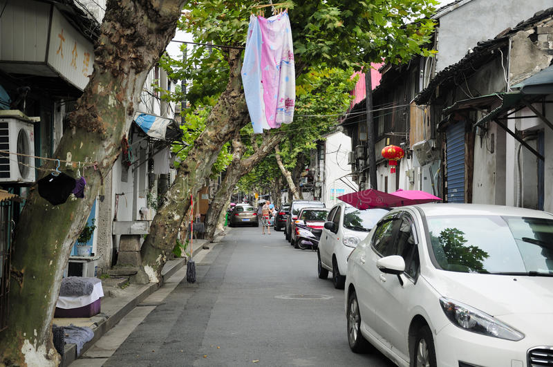 Shaoxing China. Laundry hanging from a tree on a narrow street surrounded by buildings within the city of Shaoxing China in zhejiang province stock photo