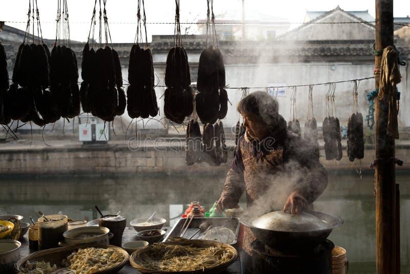 SHAOXING, CHINY: Chińska kobieta sprzedaje tradycyjnego lokalnego kluski przy starym miasteczkiem Anchang podczas zimy fotografia royalty free