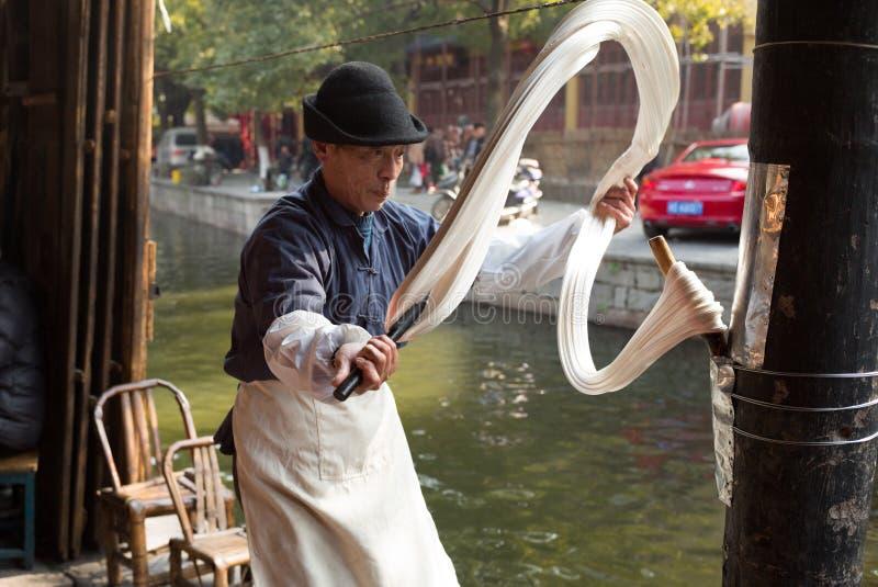 SHAOXING, CHINY: Chiński mężczyzna robi tradycyjnemu handmade smoka brody cukierkowi i sprzedaje przy starym miasteczkiem Anch obraz stock