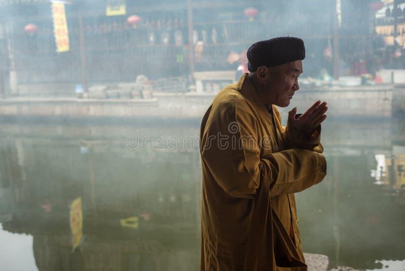 SHAOXING, CHINY: Chiński starego człowieka modlenie zdjęcia stock