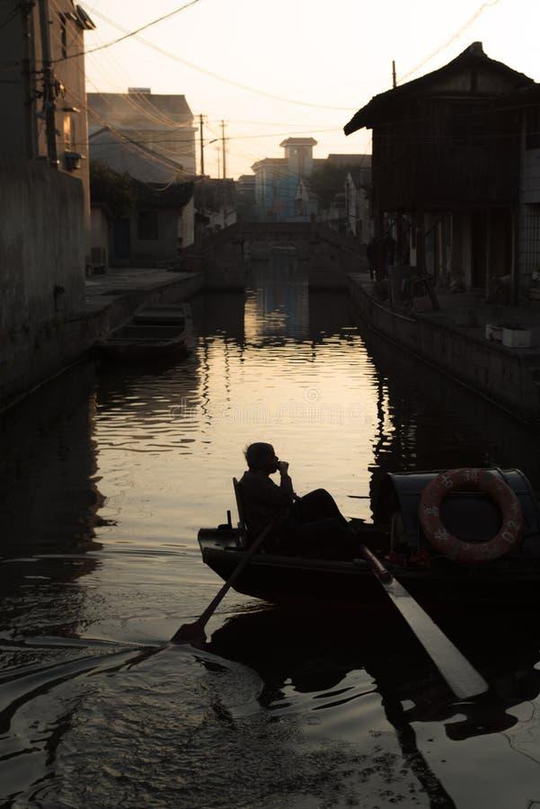 SHAOXING, CHINY: Sylwetka mężczyzny obsiadanie na wupeng markizy łódkowatej łodzi obraz stock