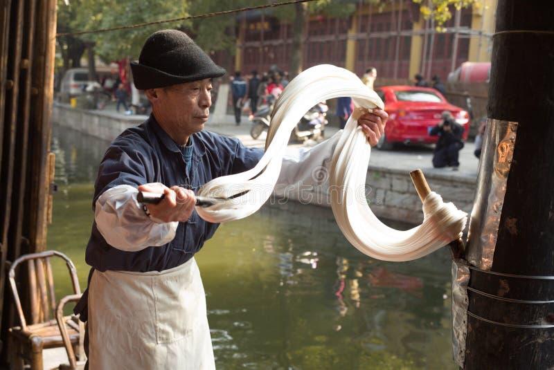 SHAOXING, CHINY: Tradycyjny słodowego cukieru ciągnięcie słodowy cukier może tak być gdy ono jest ciągnący bardzo długi, zdjęcia royalty free