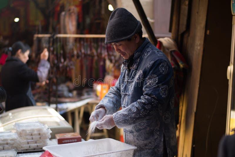 SHAOXING, CINA: Uomo cinese che produce e che vende la caramella fatta a mano della barba del drago tradizionale alla vecchia cit immagini stock libere da diritti