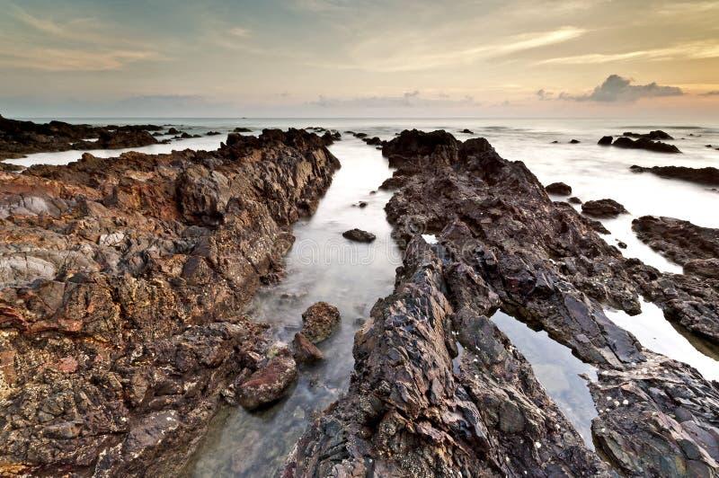 Shape av Rock på den Pandak stranden under soluppgång, Terengganu, Malaysia royaltyfria foton