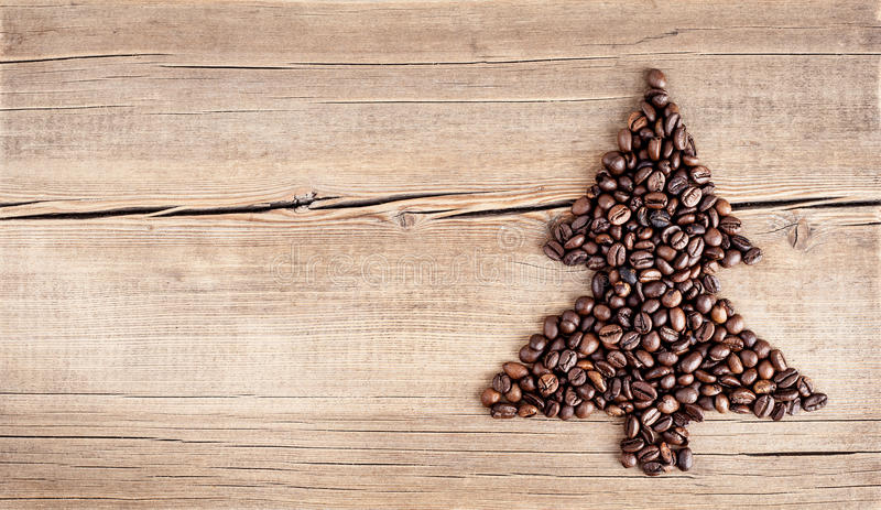 Shape of christmas tree made of coffee beans on wooden table royalty free stock images