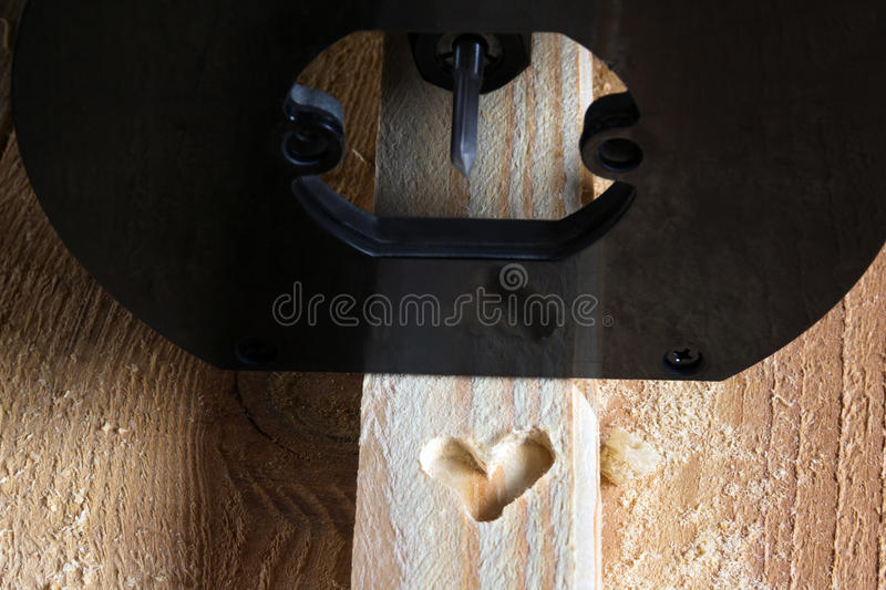 Shape of heart carved on a wood by milling cutter. Shape of heart carved on a wooden batten by milling cutter royalty free stock photo