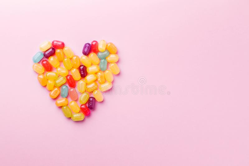 Shape of heart.Colorful lollipop caramel candy on pastel pink background.View from above.Copy space royalty free stock photography