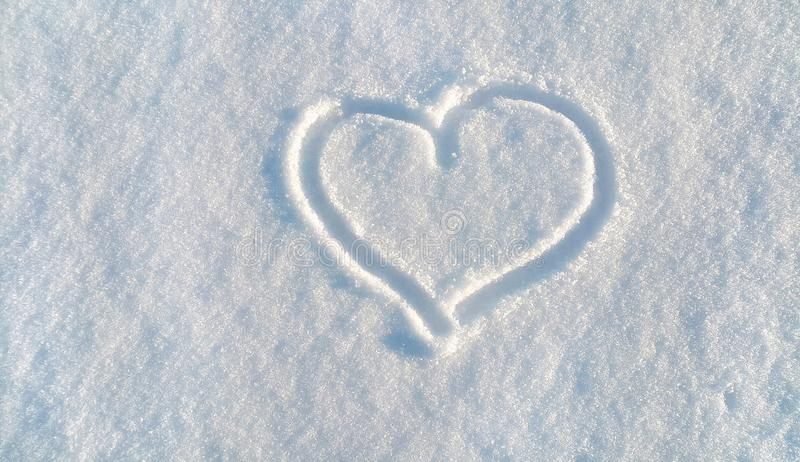 Draw of heart on the white snow. The shape of heart drawing on the white snow royalty free stock photo
