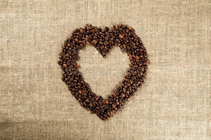 Shape of heart made of coffee beans on a burlap, top view royalty free stock photos