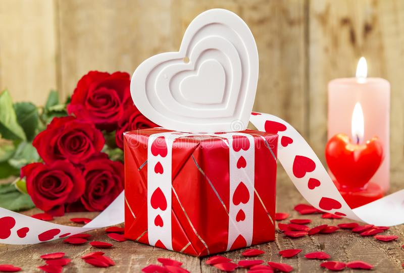 Shape of white heart in front of bouquet of red roses royalty free stock image