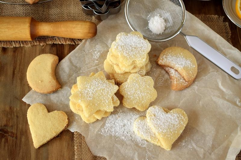 Shaped shortbread cookies covered with sugar powder. Surrounded by kitchen utensils royalty free stock image