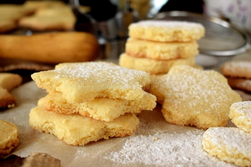 Shaped shortbread cookies covered with sugar powder. Surrounded by kitchen utensils stock photos