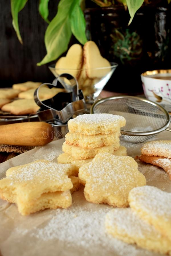 Shaped shortbread cookies covered with sugar powder. Surrounded by kitchen utensils stock images