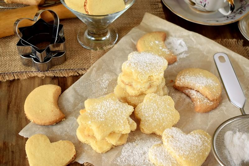 Shaped shortbread cookies covered with sugar powder. Surrounded by kitchen utensils royalty free stock photography