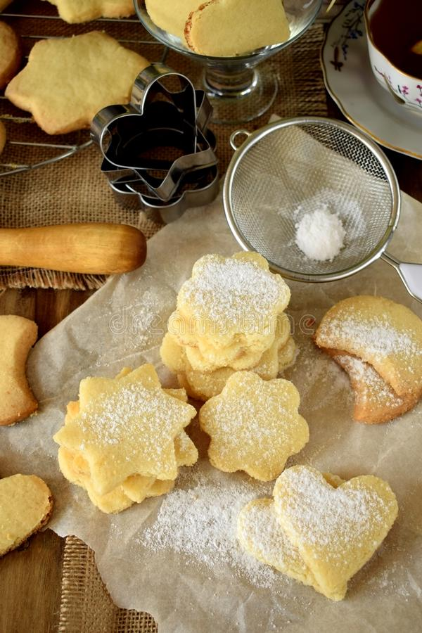 Shaped shortbread cookies covered with sugar powder. Surrounded by kitchen utensils stock photography