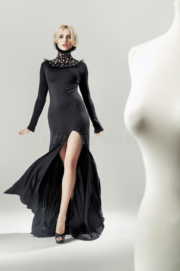 Shapely, alluring blond lady in black gown royalty free stock images