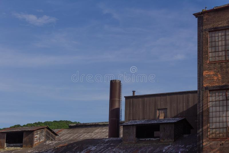 Shapes and textures of industrial buildings against a blue sky stock photography