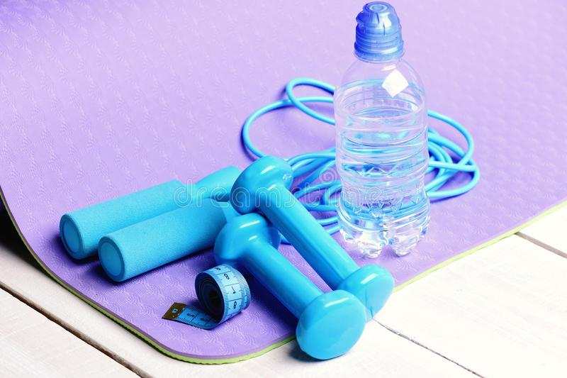 Shaping and fitness. Barbells and skipping rope next to bottle. Shaping and fitness. Barbells and skipping rope next to water bottle on purple yoga mat. Sport stock images