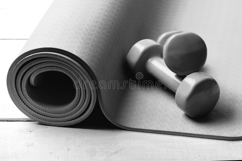 Shaping and fitness equipment. Barbells lying on purple yoga mat. Workout and sport concept. Dumbbells made of green royalty free stock photography