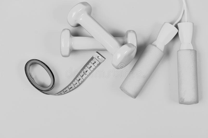 Shaping and fitness equipment, top view. Barbells and skipping rope next to measure tape roll. Sports and healthy lifestyle concept. Dumbbells and jump rope in stock photography
