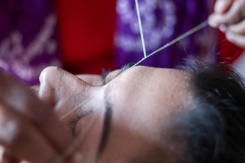 Shaping and plucking of eye brow with threading. epilation cosmetic procedure in beauty parlour stock photography